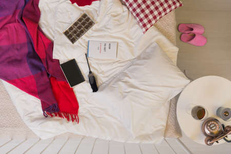 Unmade bed with a blanket and box of chocolates on it Stock Photo