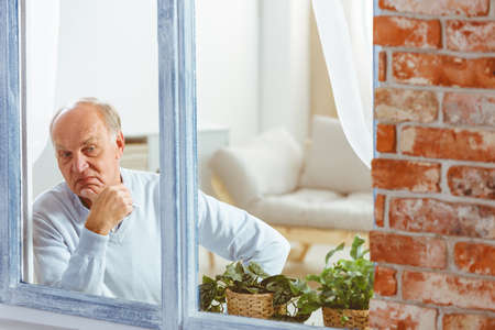 Sad wondering senior man looking out the window in apartment