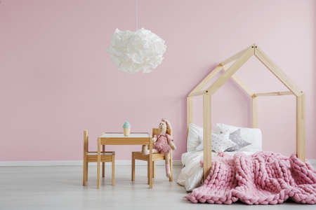 Girly scandi room with wooden house bed Foto de archivo