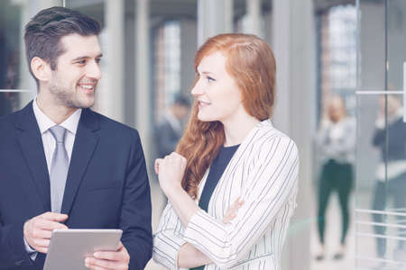 former: Young elegant woman talking with her business partner in company