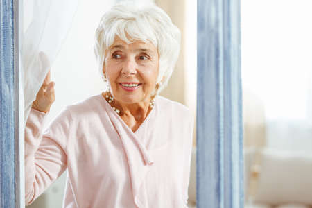 Smiling elegant woman peeping through the window Stock Photo