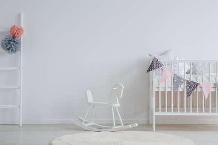 흰색 빈티지 락 말과 함께 세련된 베이비 룸