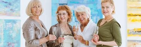 Glimlachend gekleed senior vrouwelijke vrienden drinken champagne in kunstgalerij