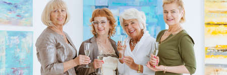 Smiling dressed up senior female friends drinking champagne in art gallery