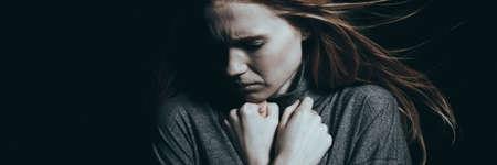 冷たい暗闇の中でうつ病を持つ孤独な女 写真素材