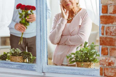 Man surprising sad senior woman staring at window with flowers Stock Photo