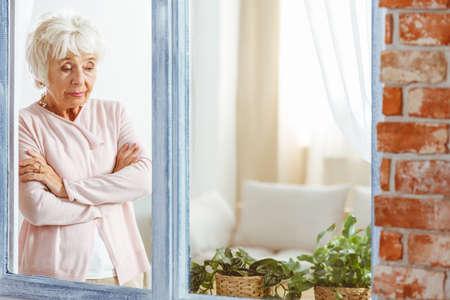 Elderly sad woman looking down wondering by the window