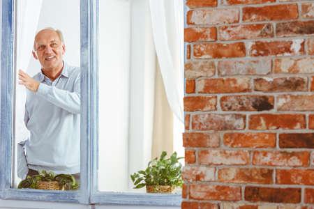 Happy smiling elegant senior man looking through window in apartment