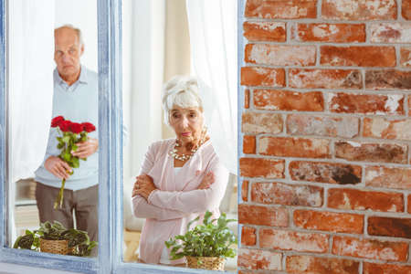 Senior man with flowers apologizing to sad elegant woman