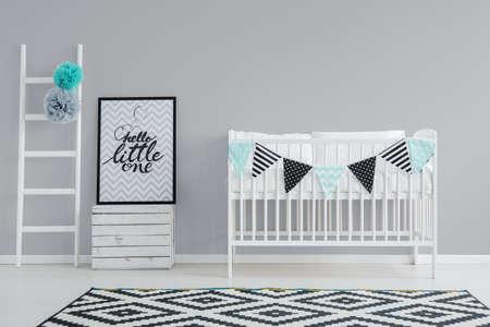 Grijze muur en witte meubels in de babykamer Stockfoto