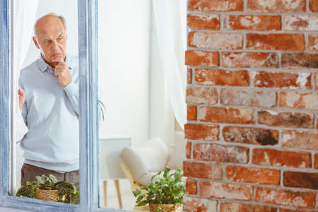 Elderly man in sweater lost in thought by the window