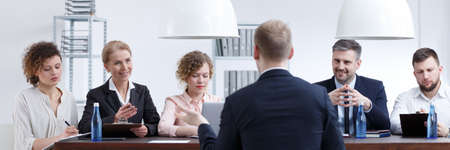 話を事務所で審査会にスーツで服を着た男