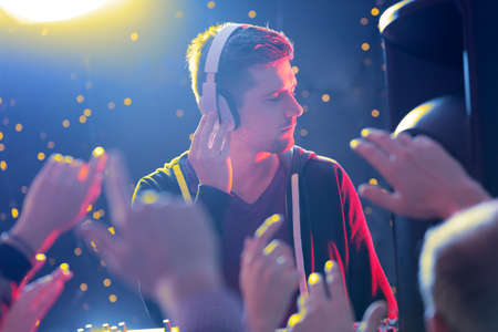 loudness: Young handsome DJ feeling the music at the club