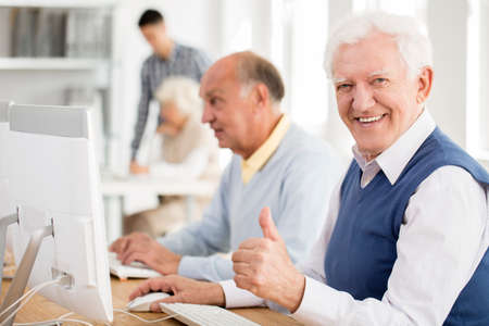 Happy grandpa enjoys learning about modern technology