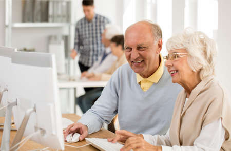 Two happy senior friends working on a computer