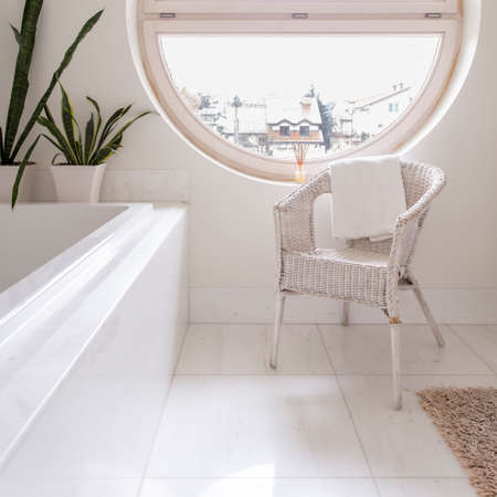 Spacious bathroom with white tiling, bathtub, chair and round window