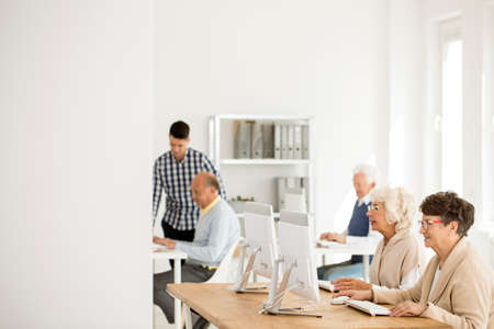 the elderly tutor: Seniors working on modern computers in the classroom