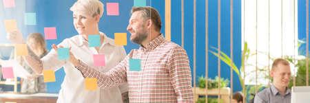 Dos personas creativas en la corporación de planificación del día con notas de colores