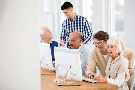 the elderly tutor: Seniors learning to use the Internet with tutors help Stock Photo