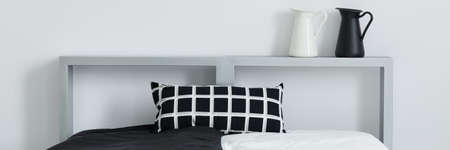 Black and white pillow with geometric pattern on the bed