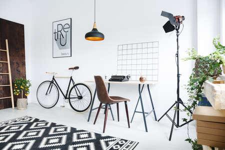 Creative modern room interior with bike, desk, typewriter and lamp
