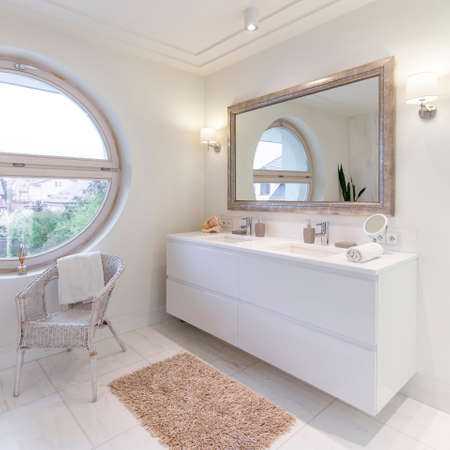 Spacious bathroom with white glossy tiles, big mirror and round window