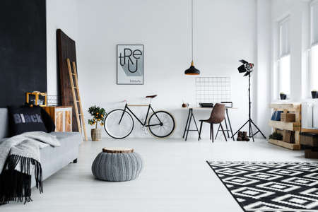 Modern spacious studio apartment with sofa, bike and desk