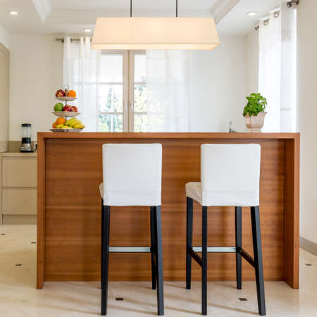 Two chairs standing beside kitchen worktop, light and spacious interior in new style