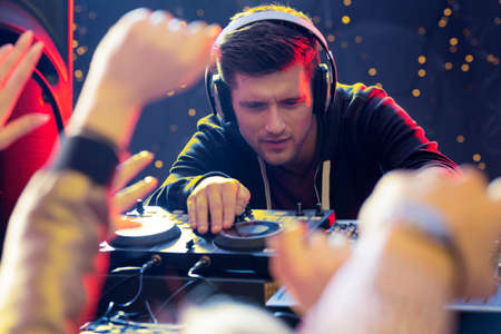 loudness: Young handsome focused DJ playing at the club Stock Photo