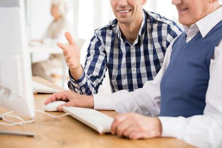Jonge docent helpen oudere man met computer taak Stockfoto