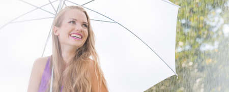 Smiling female student with umbrella during stroll in the park Stock Photo