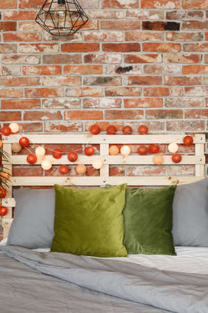 Vertical view of warm and cozy bed on a brick wall
