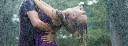Young couple happily dancing in the rain in the forest