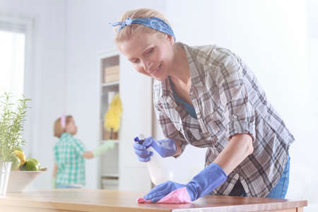 Housewife wiping the table while her daughter is dusting Stock Photo
