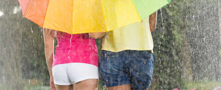 Couple under colorful umbrella during heavy summer downpour