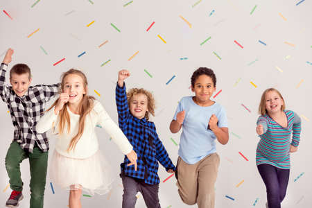 Group of young happy friends running ahead Stock Photo
