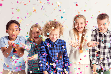 Group of sweet young kids catching colorful confetti