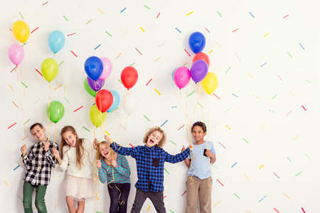 Sweet young happy kids standing with balloons