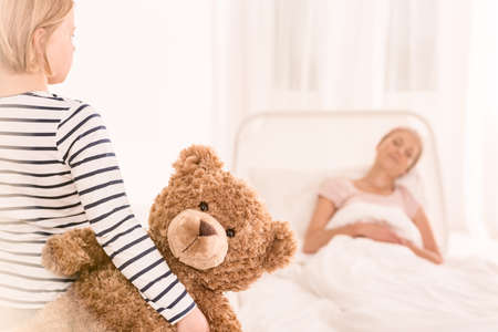 Girl with teddy bear is visiting her mother with cancer