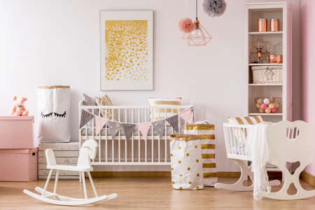 Baby nursery with a crib and golden dots pattern poster Stock Photo
