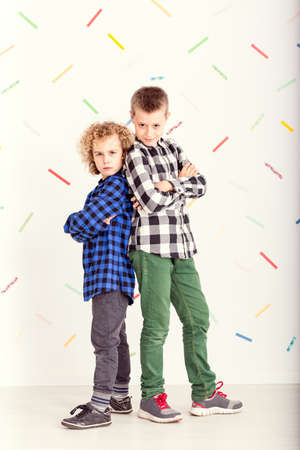 Two young boys standing back-to-back with serious faces Stock Photo