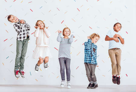 Young happy kids jumping in the playroom Stock Photo