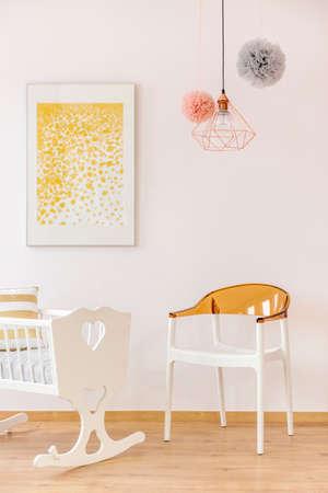 Gouden decor babykamer met poster over wieg en stoel