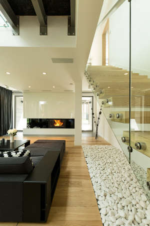 Modern living room with a couch against the fireplace, with minimalistic stairs with glazed handrail Imagens