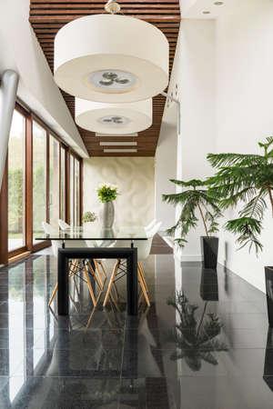 Elegantes lámparas blancas en techo de madera en comedor moderno.