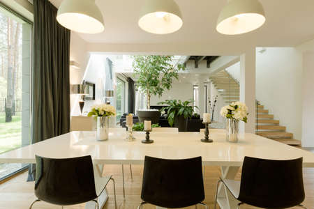 Modern dining room witch a big table, minimalistic chairs and with the view of the living room and patio entry