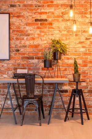 Black frame mockup poster on brick wall over industrial desk