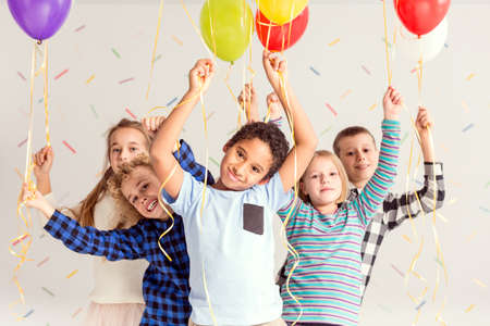 Group of young sweet friends holding colorful balloons