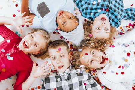 Gelukkige kleine kinderen liggen samen op de grond Stockfoto