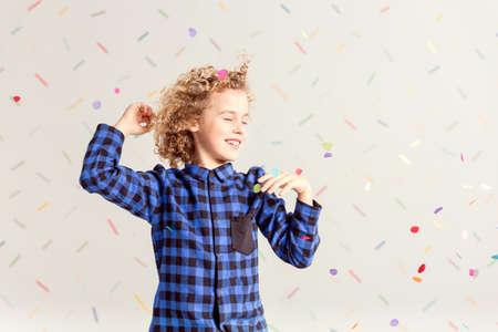 Sweet little boy dancing with confetti falling down